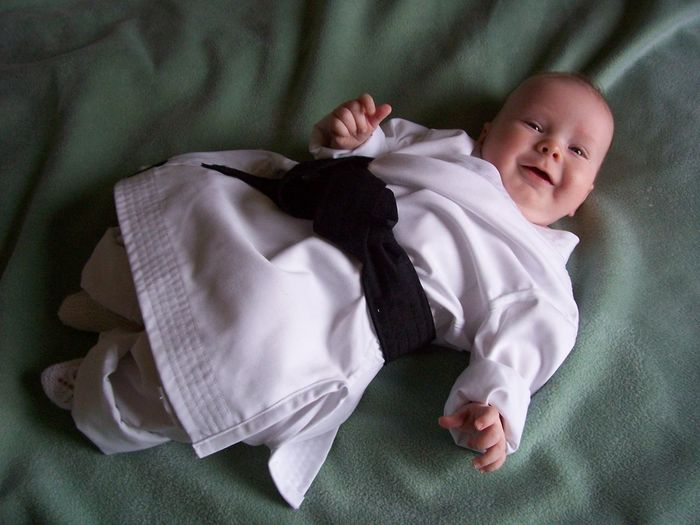 High angle view of child with black belt lying down on green blanket