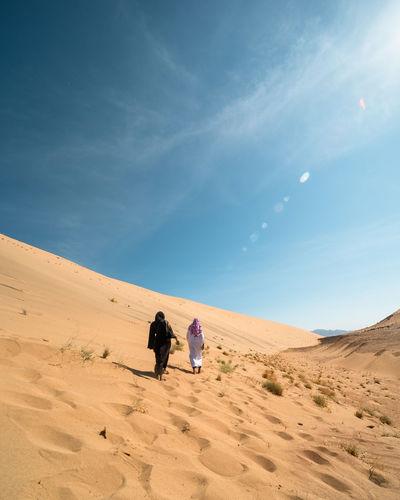 People on sand dune in desert against sky