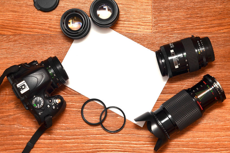 Directly above shot of modern camera and blank paper on wooden table
