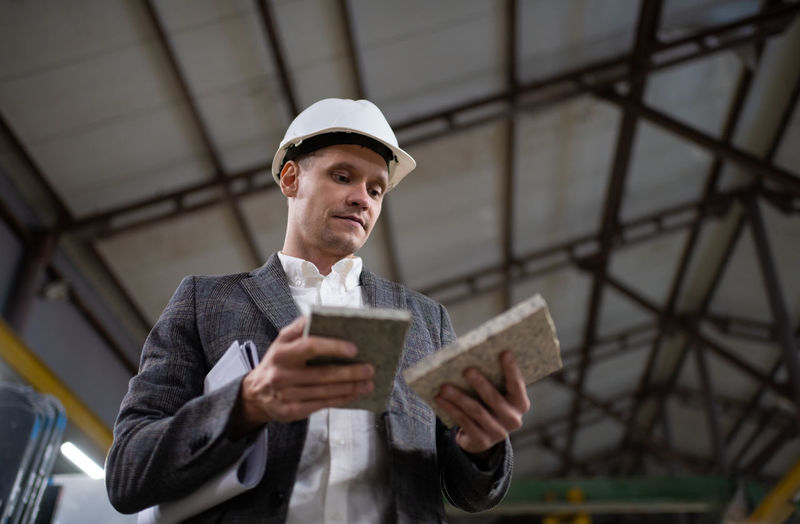 Low angle view of man holding paper
