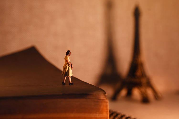 Dream Destination for Vacation. Travel in Paris, France. a Miniature Tourist Woman Standingon the Aged Book and Looking at the Eiffel Tower. Vintage Style Paris Travel Concept Miniature Eiffel Tower Tourist Woman Solo Single Figure Europe France Tourism Summer City Female Famous person Young Traveler Dreaming Planing Guidebook Destination Landmark Happy Fashion European  French Girl Place Sightseeing Lifestyle Vacation Trip Traveller Romantic Sign Closeup Macro Photo Mini Full Length Standing Women