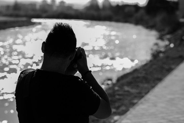 Rear view of man photographing river