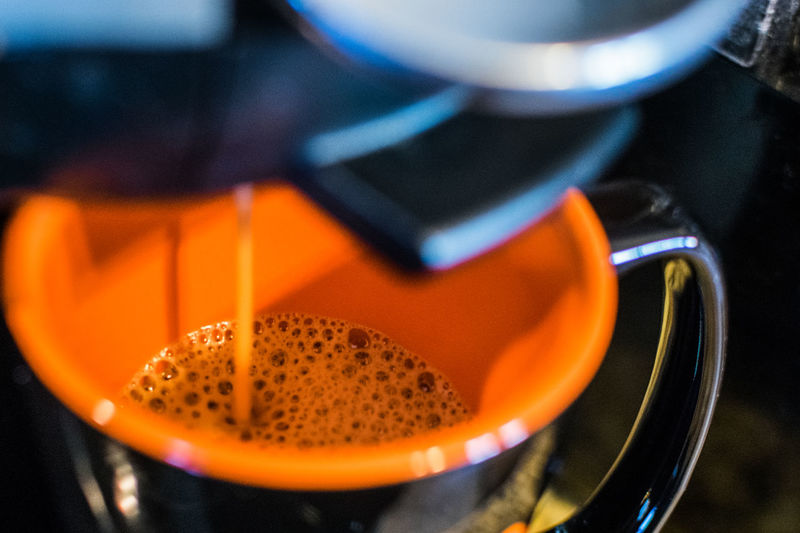 Close-up of espresso maker pouring coffee in cup