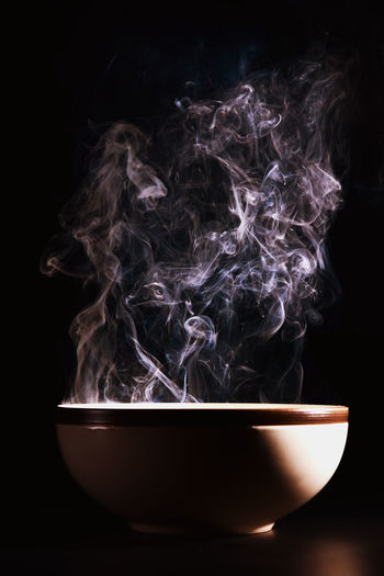 Picture of smoke rising from the food above the cup The concept of hot food. Black Background Studio Shot Indoors  Heat - Temperature Burning Smoke - Physical Structure No People Motion Close-up Bowl Nature Illuminated Copy Space Food And Drink Fire Fire - Natural Phenomenon Flame Food Abstract Steam Mixing