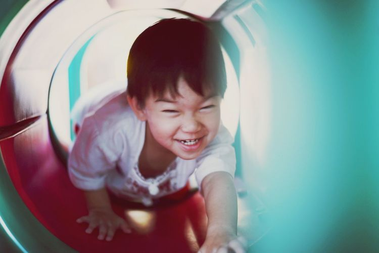 Portrait of happy boy playing in slide