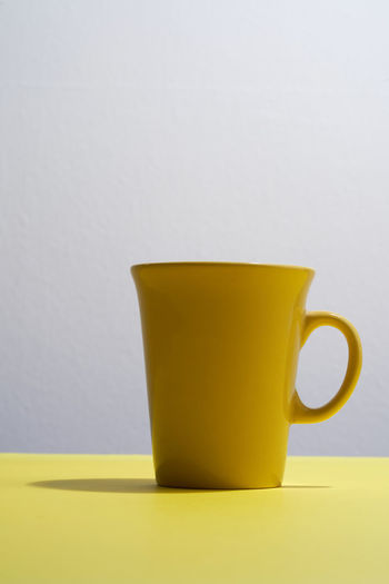 Close-up of coffee cup on table against white background