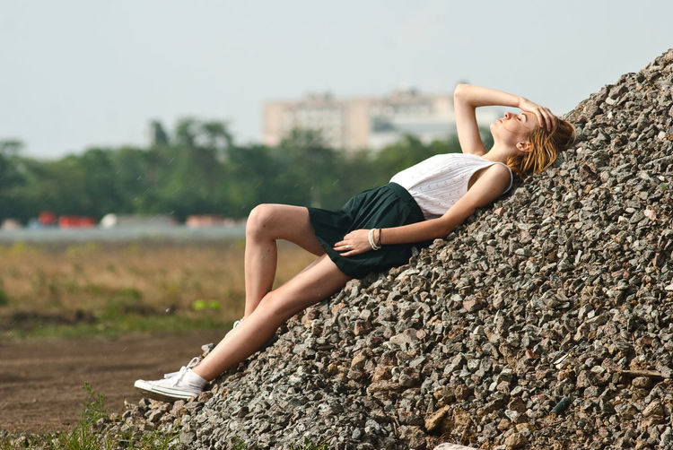 Woman lying on rocks against sky
