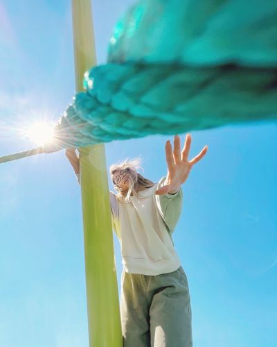 Low angle view of woman standing against sky on sunny day