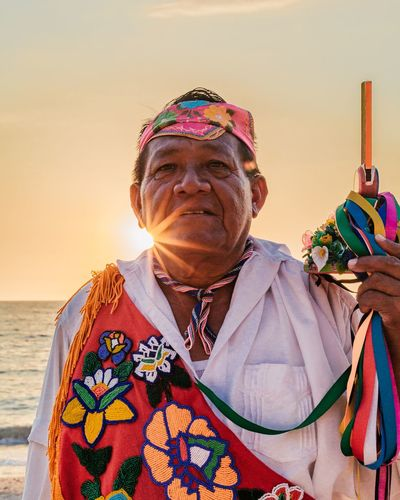 Portrait of man holding multi colored umbrella against sky during sunset