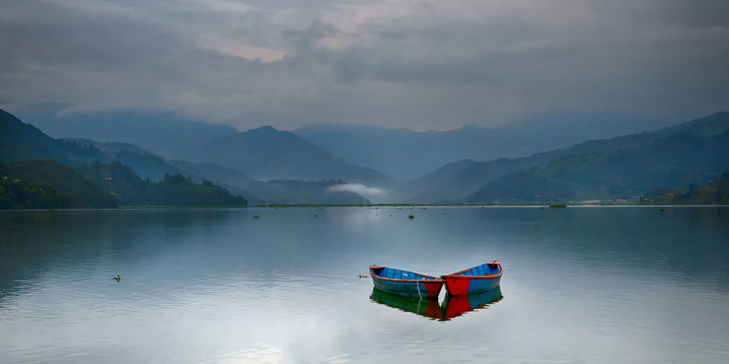 Rowboat moored in lake by mountains against cloudy sky