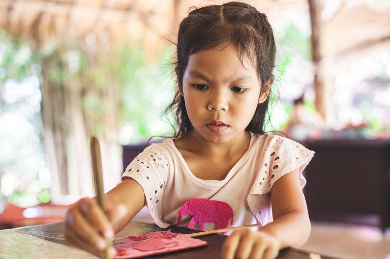 Close-up of cute girl making artwork at workshop