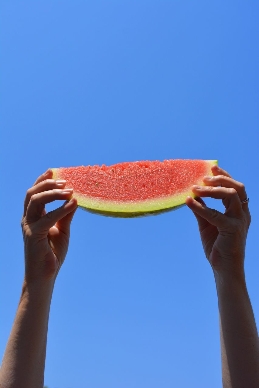 human hand, healthy eating, holding, slice, fruit, copy space, watermelon, clear sky, freshness, food and drink, one person, healthy lifestyle, blue, human body part, food, studio shot, outdoors, lifestyles, day, real people, close-up, ready-to-eat, people