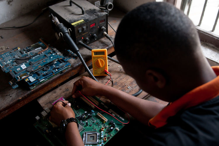 Young adult repairing a computer motherboard in a workshop