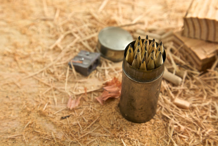 High angle view of pencils in container on hay