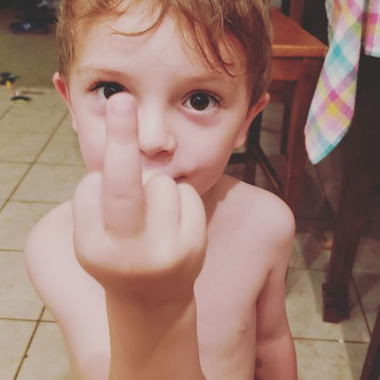 Portrait of shirtless boy showing obscene gesture at home