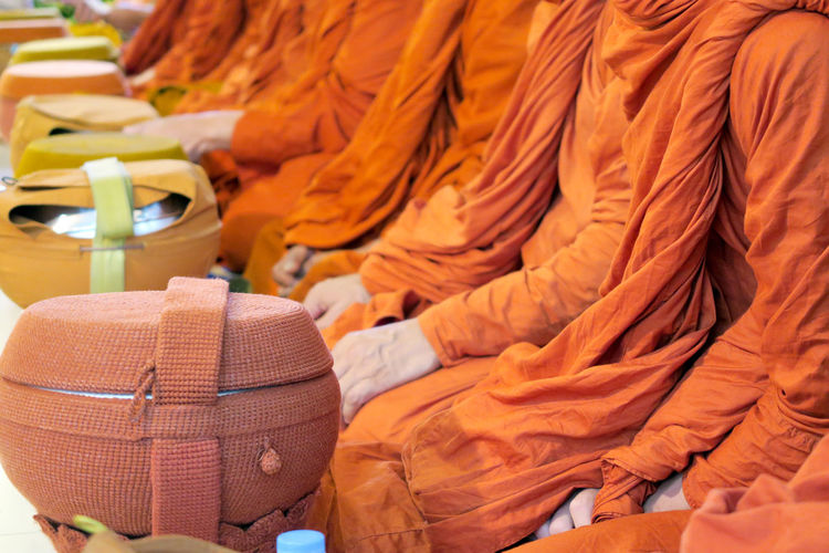 Midsection of monks with container sitting in row