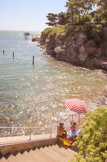 Sea Water Day Nature Outdoors Atlantic Ocean Loire Atlantique Ocean Waterfront Seaside Real People Lifestyles Sunlight Men Child Women Leisure Activity Two People Family People Childhood Umbrella Sitting Incidental People Sunny Holidays Stairs Rock Formation Fishing Hut