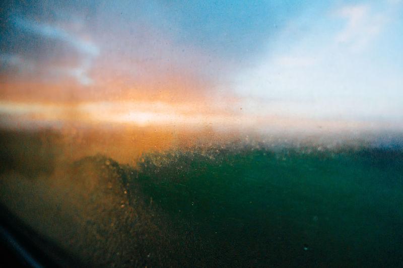 Raindrops on glass window during sunset