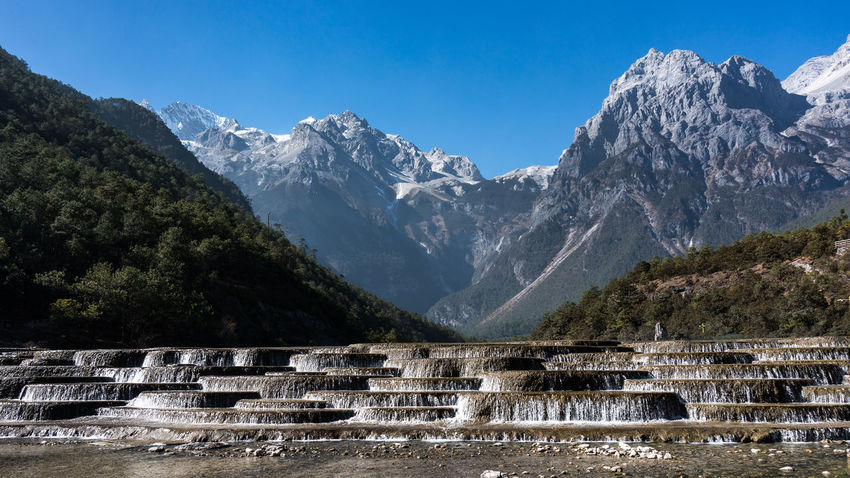 Jade Dragon Snow Mountain,Mount Yulong or Yulong Snow Mountain at Lijiang,Yunnan province,China. Architecture Beauty In Nature Clear Sky Cold Temperature Day Landscape Mountain Mountain Range Nature No People Outdoors Scenics Sky Snow Sunlight Tranquil Scene Tranquility Tree
