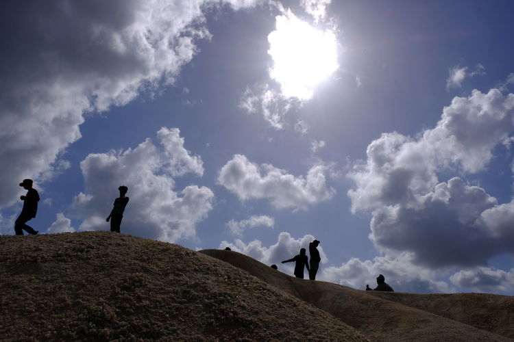 Low angle view of silhouette people walking on land against sky