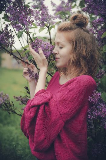Woman standing by purple flowering plants