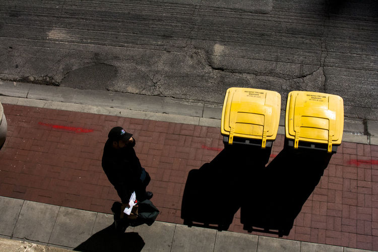 High angle view of man walking by yellow garbage cans on sidewalk