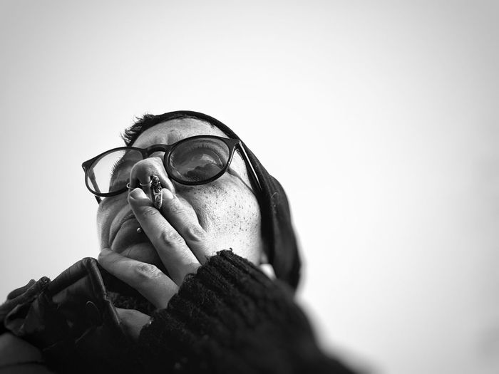 Close-up of woman smoking cigarette against clear sky