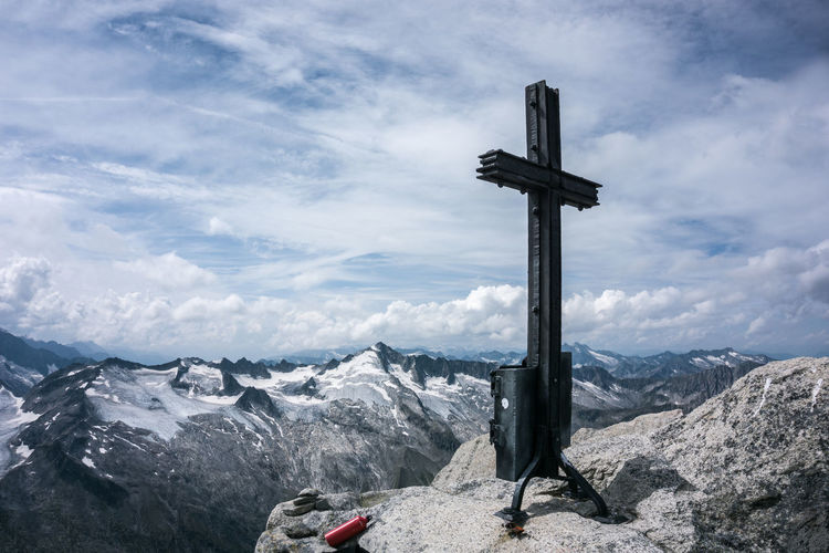 Cross on rock by snowcapped mountains against sky