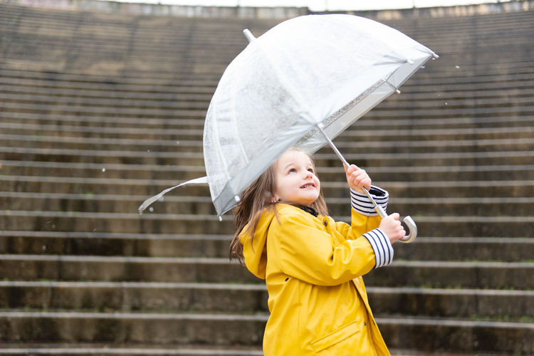 Girl holding umbrella while standing outdoors