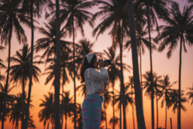 Silhouette woman standing by palm trees against sky during sunset