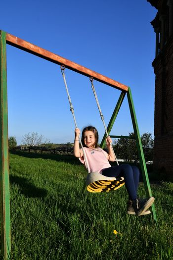 Girl playing on swing in playground