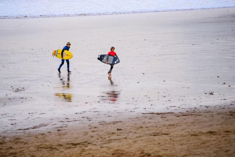 Rear view of people enjoying on beach