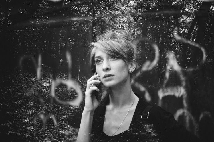 Double exposure of young woman talking on phone and trees at forest