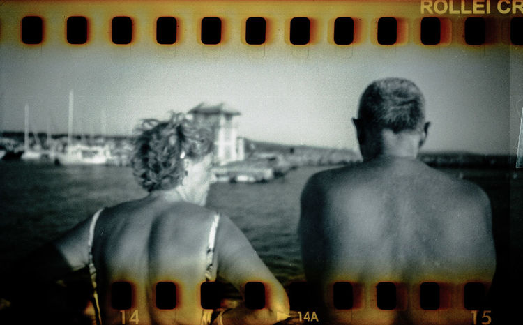 From here. Wrongly-processed Rollei CR200 slide film, shot in a modified Holga 120 camera. Ways Of Seeing 35mm Analogue Analogue Photography BW_photography Couple Holga Holga Photography Analog Bw Bw Photography Candid Couple - Relationship Day Film Photography People Rear View Sprocket Holes Street Photography Streetphotography Rear View Human Representation Adult Side By Side Waist Up Focus On Foreground