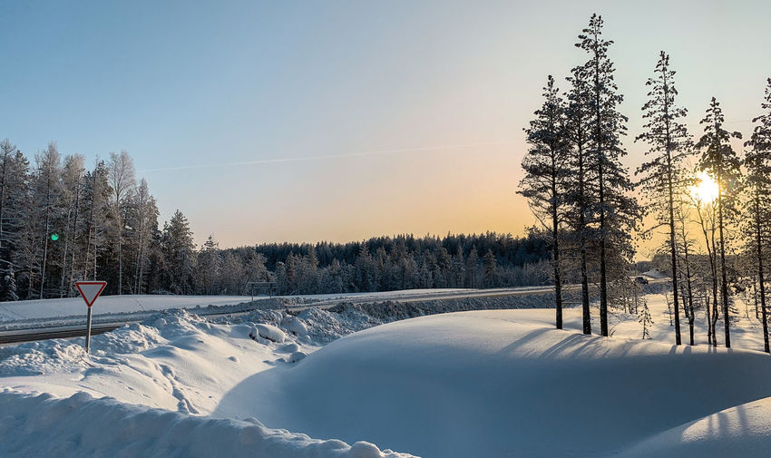 Snow covered field against sky during sunset