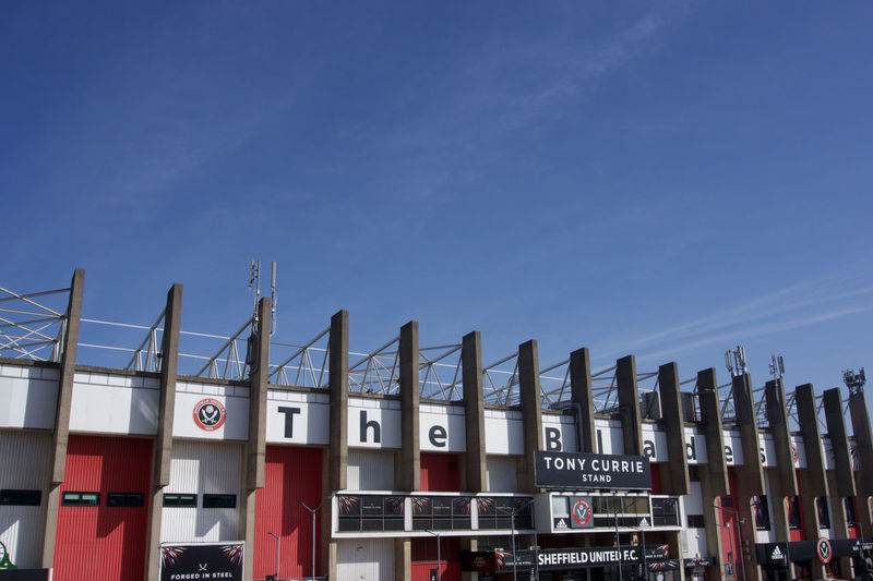Exterior view of Tony Currie Stand at Bramall Lane Football Ground, Sheffield United.on a sunny day with blue sky and copy space Sheffield Sheffield United Bramall Lane Football Stadium Ground Standing Yorkshire Blades Sky Text Architecture Day No People Building Exterior Western Script Communication Built Structure Copy Space Low Angle View Outdoors Sign City Blue