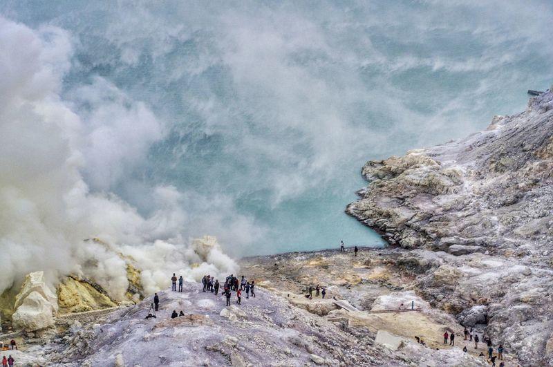 Group of people on rock in kawah ijen volcano