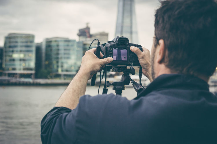 Rear view of man photographing by river in city