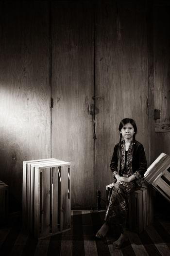 Girl sitting against wall