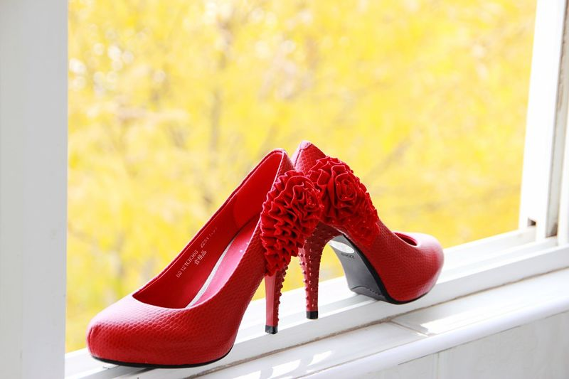 Red high heels on window sill