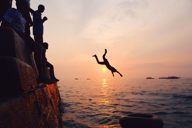 Take a leap of faith. Ocean Africa Water Reflections Sunset Sunset Silhouettes Outdoors Water Children Fun Landscape