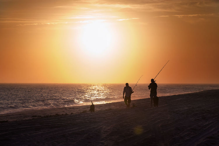 Silhouette men fishing at beach against sky during sunset