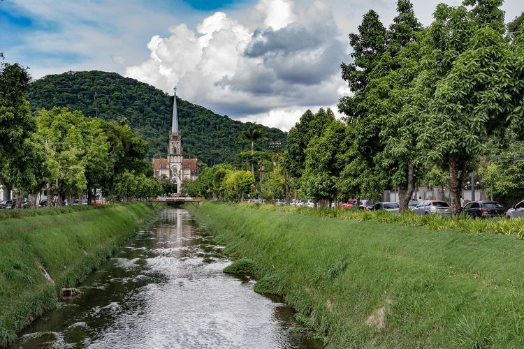 Stream Leading Towards Church By Tree Mountain Against Sky