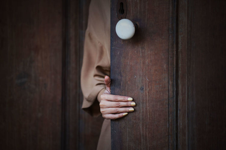 Close-up of woman holding door