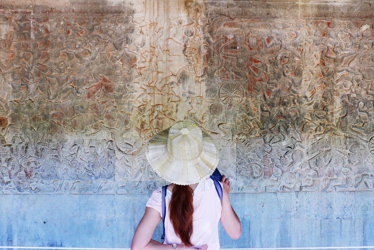 Rear view of woman looking at ancient text on angkor wat wall