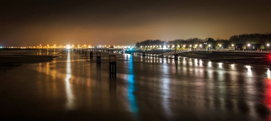 Scenic View Of Beach With Light Reflections At Night