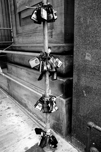 High angle view of padlocks hanging on railing against wall
