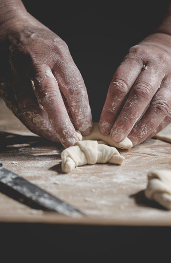 Senior woman cooks Christmas pastries POV Share Food Baking Candid Christmas Pastry Detail Dough Egg Flour Food Freshness Human Hand Kneading Making One Person Pouring Water Preparation  Real Life Real People Rolling Croissant Senior Woman Splash UNPOSED Unstereotyp Vintage