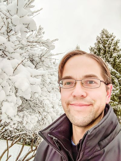 Portrait of smiling young man in snow