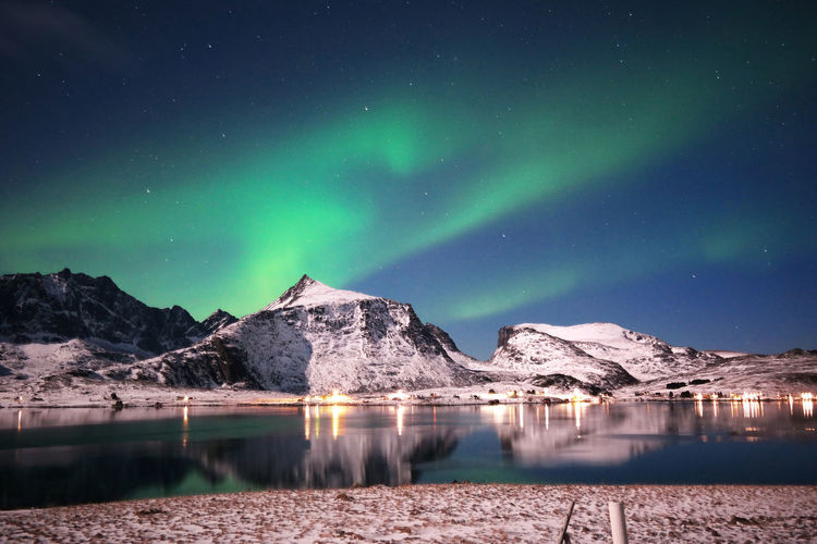 Stunning dancing northern lights over snowy mountains and sea coast in lofoten islands, norway.